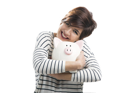 Beautiful happy woman with a piggybank, isolated over a white background