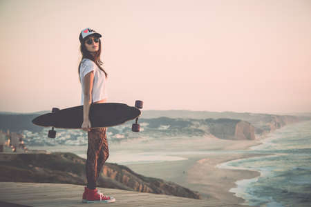longboard: Beautiful fashion skater girl posing with  a skate board Stock Photo