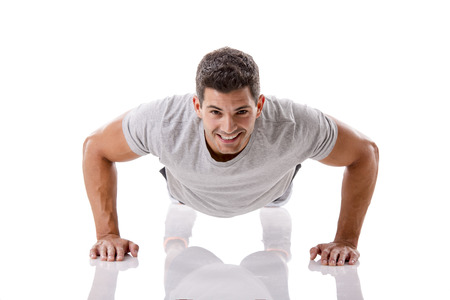 Man making pushups in studio, isolated over a white background photo