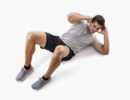 Athletic man doing abdominals, isolated over a white background photo
