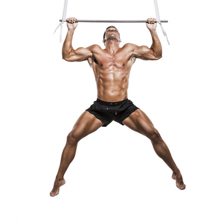 full suspended: Muscle man making elevations, isolated over a white background