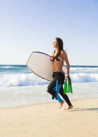 bodyboard: A beautiful girl running at the beach with her bodyboard