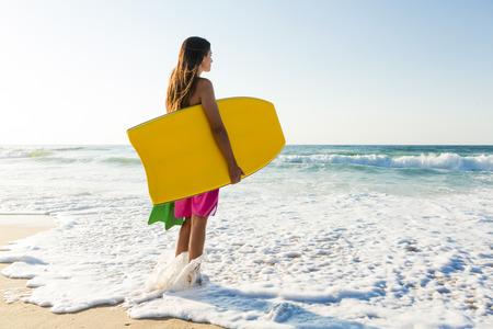 bodyboarder: A beautiful girl at the beach with her bodyboard