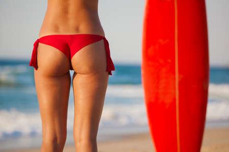 culo donna: Vista posteriore di una donna sexy in bikini con sua tavola da surf Archivio Fotografico