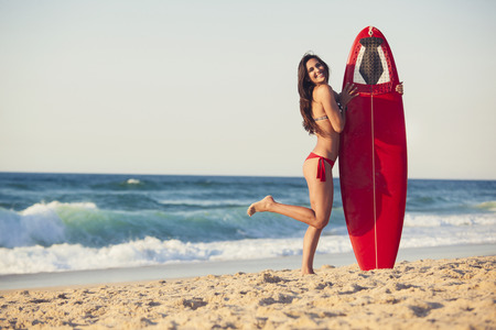 A beautiful girl at the beach holding her surfboard photo