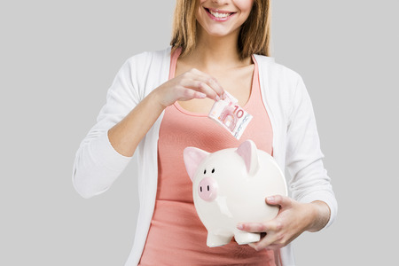 Beautiful woman putting money in a piggy bank, isolated over white background photo