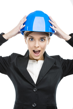 Fuuny portrait of young female engineer with hands holding a blue helmet photo
