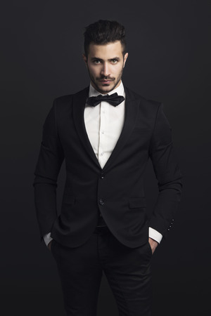 Portrait of a beautiful latin man smiling wearing a tuxedo photo
