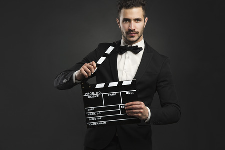Portrait of a beautiful latin man with tuxedo and holding a clapboard photo