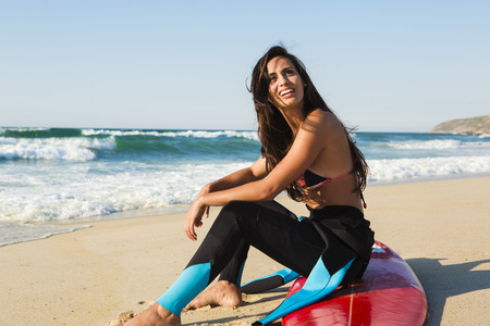 Beautiful surfist sitting over her surfboard photo