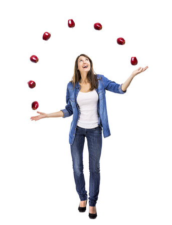 Healthy woman throwing apples, isolated over a white background photo