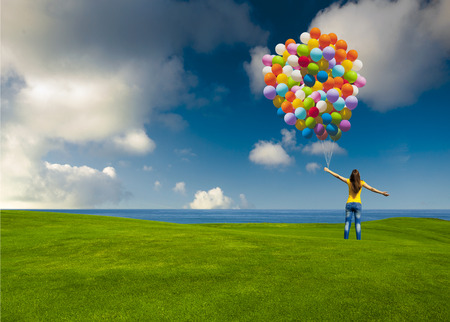 Happy young woman with colorful balloons on a green meadow Stock Photo - 29917353