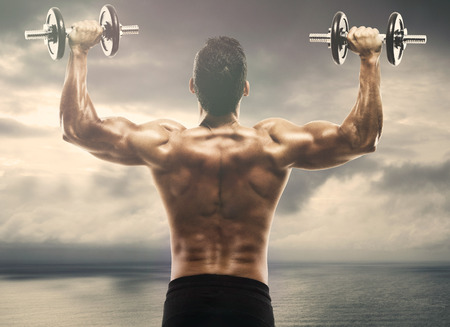 Muscle man lifting weights on outdoor photo