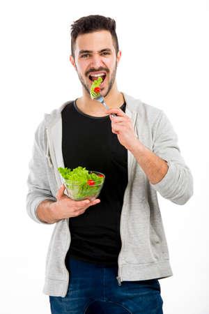 Giovane felice che mangia un'insalata, isolato su sfondo bianco