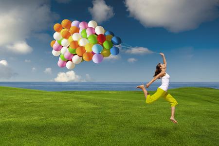 Ragazza bella e atletica saltando con palloncini su un prato verde