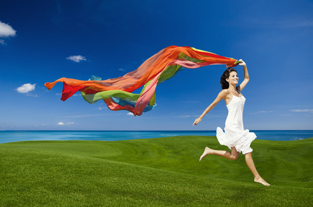 Beautiful woman jumping on a green meadow with colored tissues Stock Photo