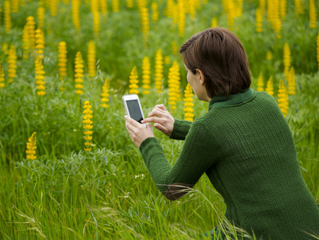 Woman taking pictures to flowers with a cellphone Stock Photo - 29917404