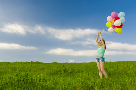 fluctuate: Young beautiful woman with colorful balloons on a green meadow