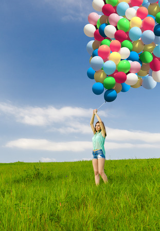 Young beautiful woman with colorful balloons on a green meadow photo