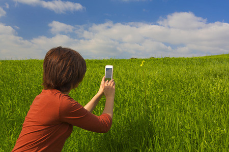 Woman in outdoor taking a photo with the cellphone Stock Photo - 29917509