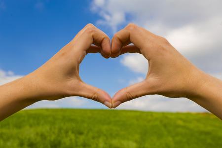 Female hand making a heart shape against a beautiful blue sky Stock Photo - 29917511