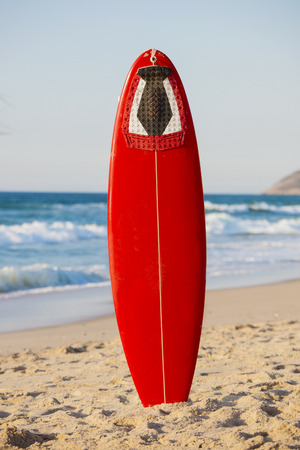 surfboard fin: Red surfboard on the sand on a very beautiful sunny day Stock Photo