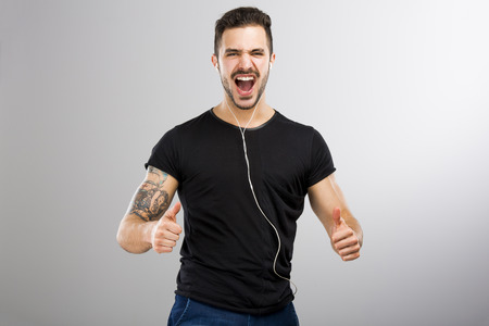 brawny: Beautiful and happy latin man listen music with thumbs up