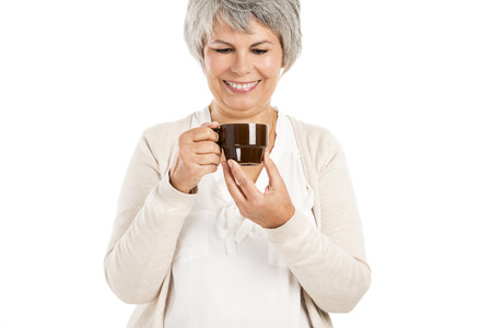 Happy elderly woman holding and drinking a cup of coffee photo