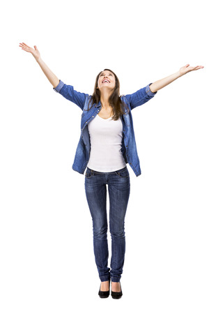 raised arms: Happy woman trying to catch something falling from the sky Stock Photo