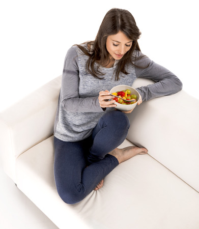 Beautiful woman relaxing on the sofa and eating a fruit salad photo