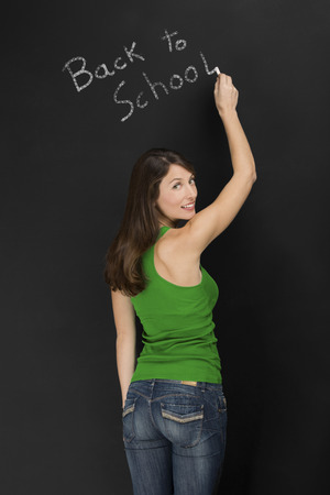 Beautiful young student writing on chalkboard the words back to school photo