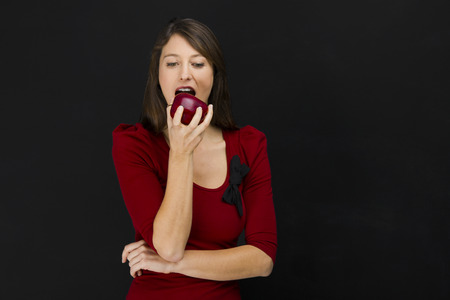 over eating: Beautiful young woman eating a fresh red apple, over a black background Stock Photo