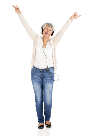 gaiety: Happy elderly woman listen music with headphones, isolated over white background Stock Photo