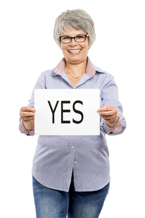 voting paper: Elderly woman holding a paper card  with the word Yes Stock Photo