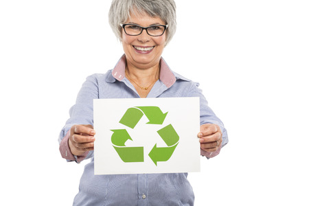 older woman smiling: Elderly woman holding a paper card  with the recycling sign