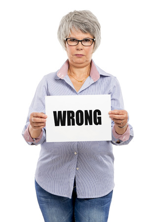 Elderly woman holding a paper card  with the word Wrong photo