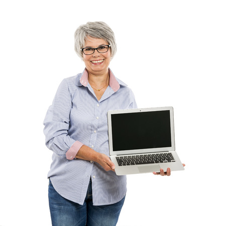 gaiety: Happy elderly woman holding and showing something on a laptop Stock Photo