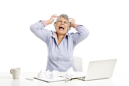 computer problem: Stressed elderly woman working in the office with a laptop Stock Photo