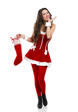 santa girl: Beautiful and sexy woman wearing santa claus costume and carrying a christmas sock Stock Photo