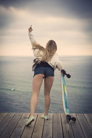 Beautiful fahions girl holding a skateboard  and showing a finger Stock Photo