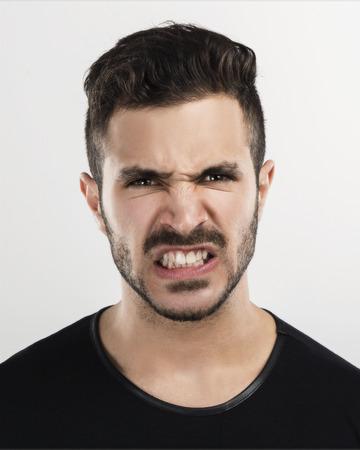 caras tristes: Estudio de retrato de un hombre joven y guapo con una expresión atónita enojado