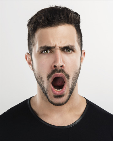 man screaming: Studio portrait of a handsome young man shouting out loud