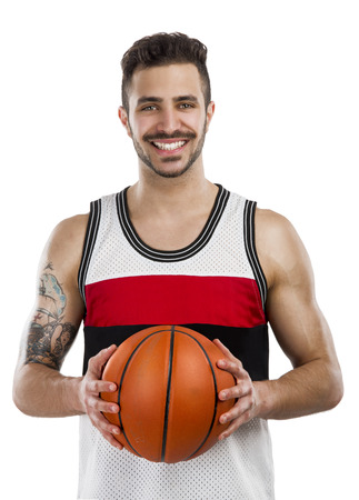 basket ball: Athletic man holding a basket ball and smiling, isolated over a white background Stock Photo