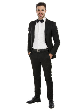 Handsome young man wearing a suit and smiling, isolated on white background photo