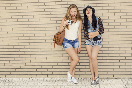 Two beautiful and young girlfriends having fun, in front of a brick wall photo
