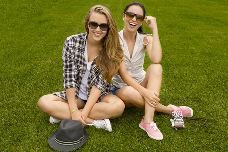 Female best friends sitting on the grass and having a good time photo