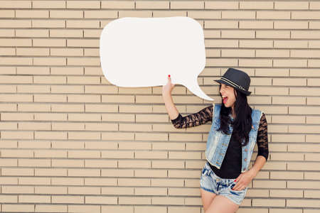 talk show: Beautiful and young teenager holding a thought balloon, in front of a brick wall
