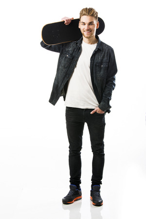 boy skater: Studio portrait of a young man posing with a skateboard
