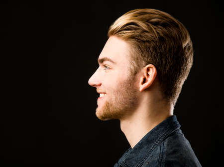 from side: Studio portrait of a young fashion man Stock Photo