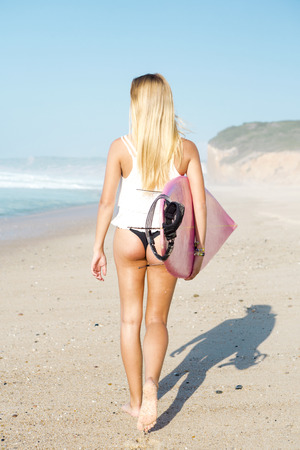 one teenager: A beautiful surfer girl walking at the beach with her surfboard